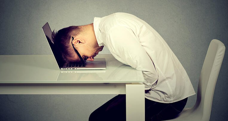 Man banging head on desk