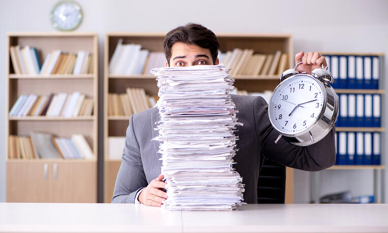 Man with Paper Pile shutterstock_557612260