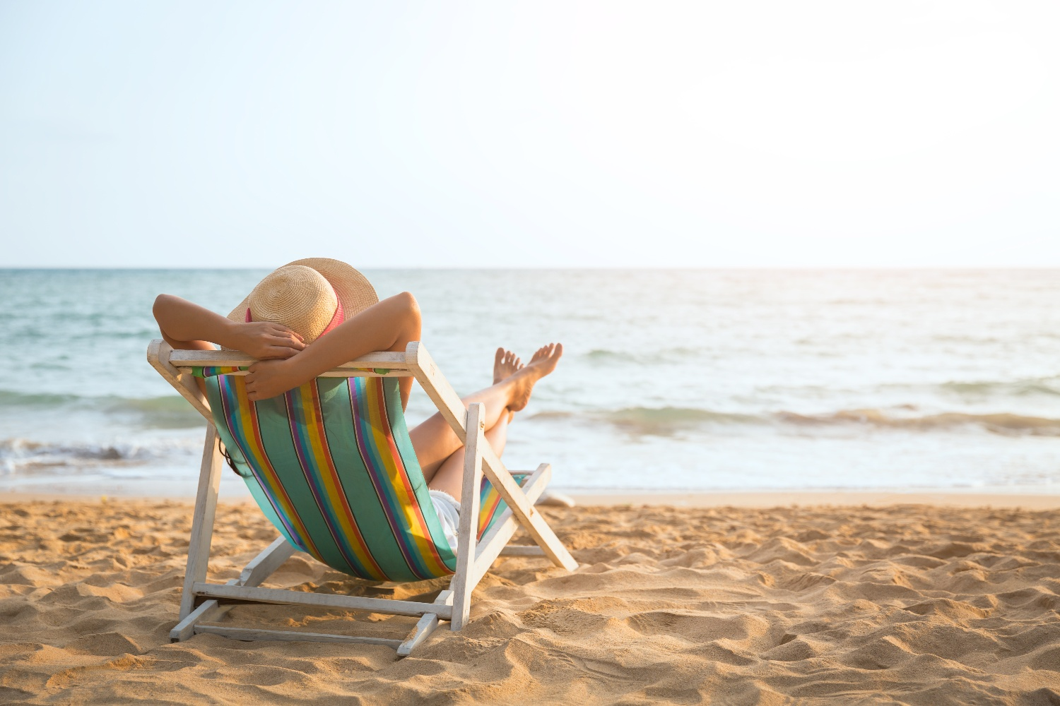 person in lounge chair on the beach