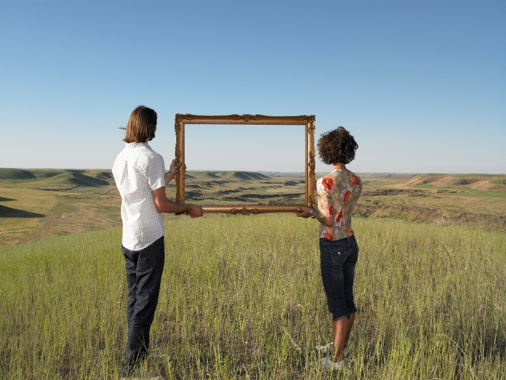 Two people looking through a frame