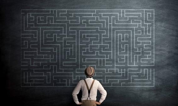man in front of chalkboard maze