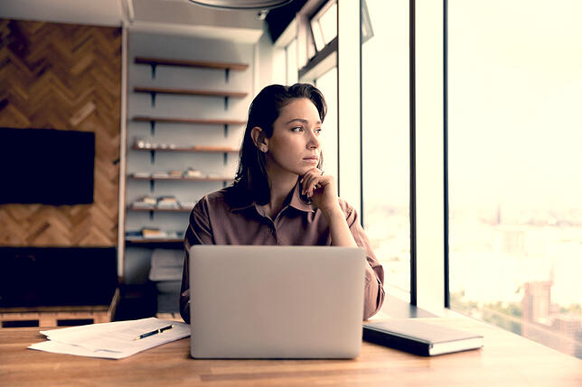 woman at desk staring out window shutterstock_2022462290