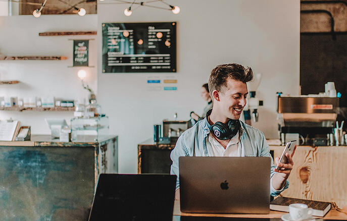 a worker working at a computer in a coffee shop